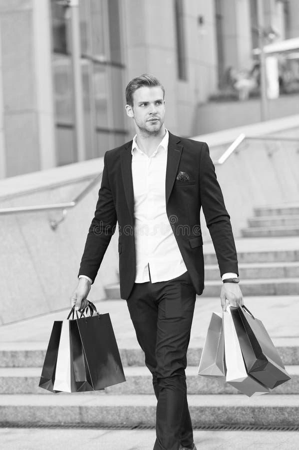 Compras de lujo Cliente de la galería del boutique El comprador del hombre lleva el fondo urbano de los panieres Hombre de negoci fotos de archivo