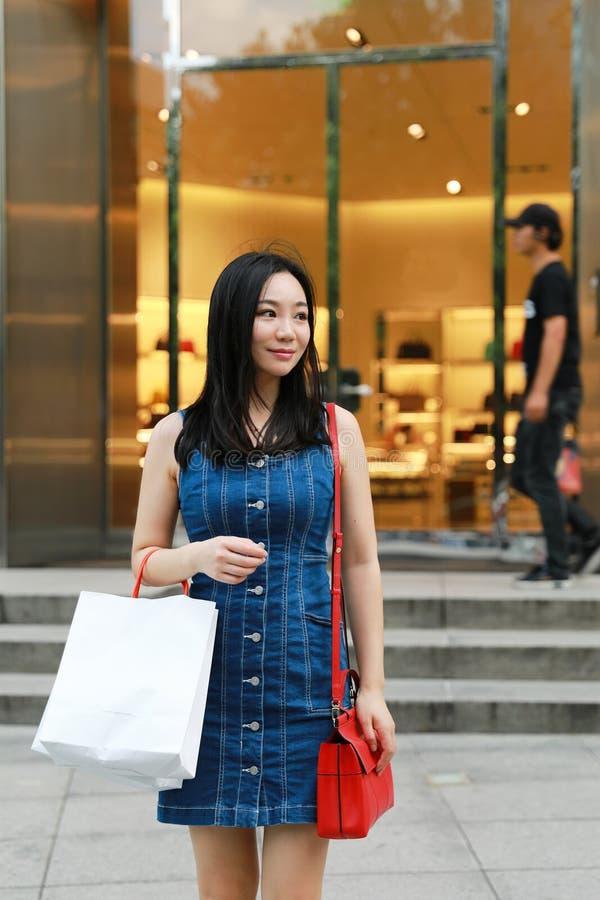 Compras de moda jovenes orientales del este chinas felices de la muchacha de la mujer de Asia en alameda con el fondo de la venta fotografía de archivo libre de regalías