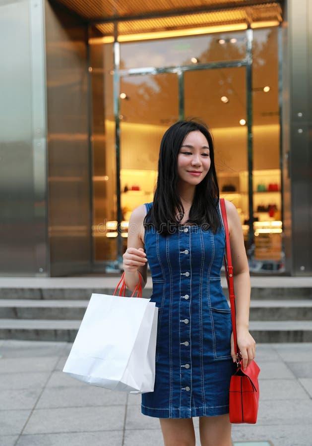 Compras de moda jovenes orientales del este chinas felices de la muchacha de la mujer de Asia en alameda con los bolsos delante d imágenes de archivo libres de regalías