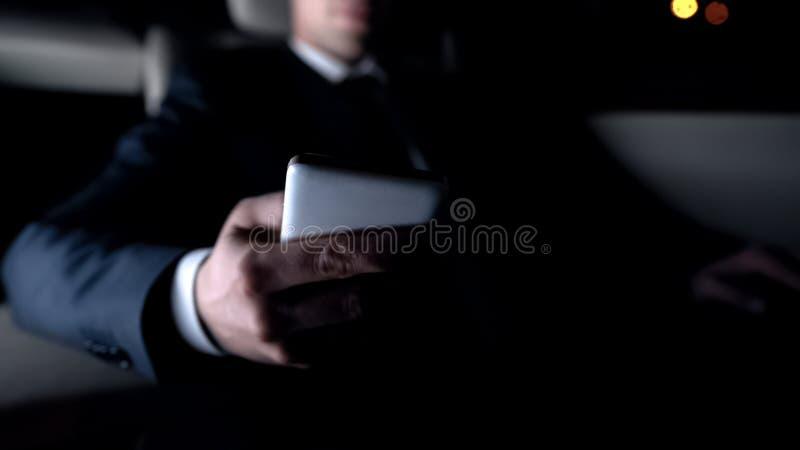 Compras del hombre de negocios en línea mientras que conduce la aplicación móvil casera, nueva, cierre para arriba fotos de archivo libres de regalías
