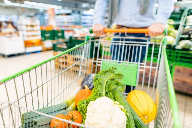 Compras del hombre en el supermercado que empuja su carretilla con las verduras imagenes de archivo