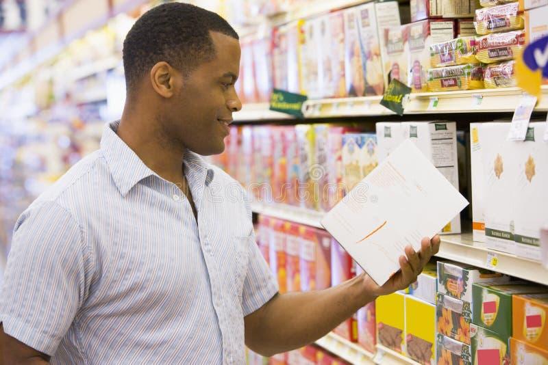 Compras del hombre en supermercado foto de archivo