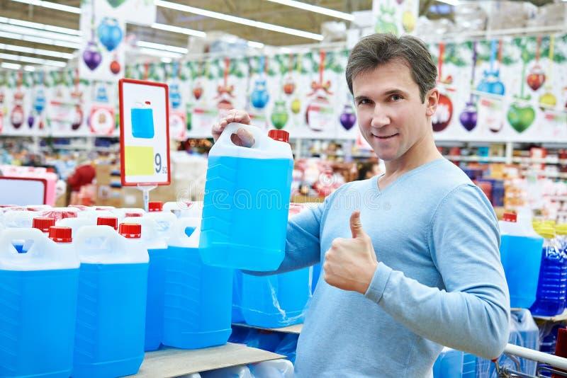 Compras del hombre nonfreezing el líquido en supermercado fotos de archivo