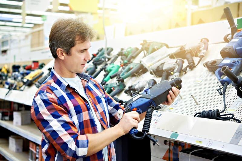 Compras del hombre para el perforador en ferretería imagen de archivo libre de regalías