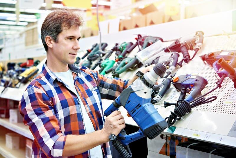 Compras del hombre para el perforador en ferretería foto de archivo