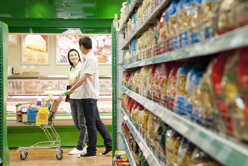 Compras del hombre y de la mujer en un supermercado con el carro de la compra imagen de archivo