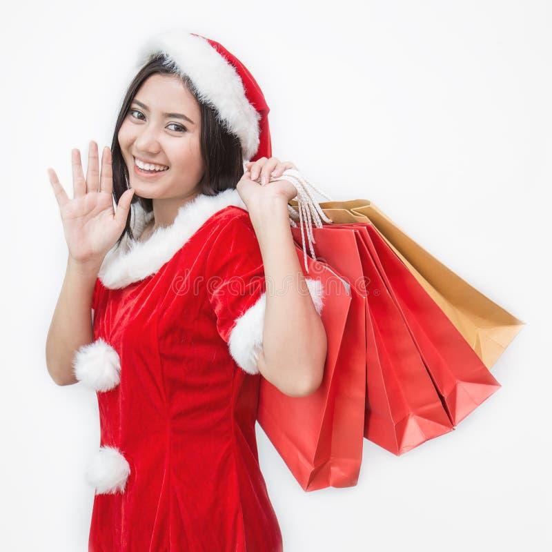 Compras del invierno de la Navidad Mujer asiática en el sombrero de Papá Noel que se coloca que sostiene los panieres imágenes de archivo libres de regalías
