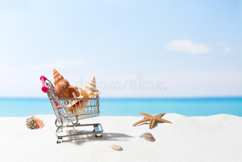 Compras del verano Negocio y venta en la playa Carro en la arena blanca imagenes de archivo