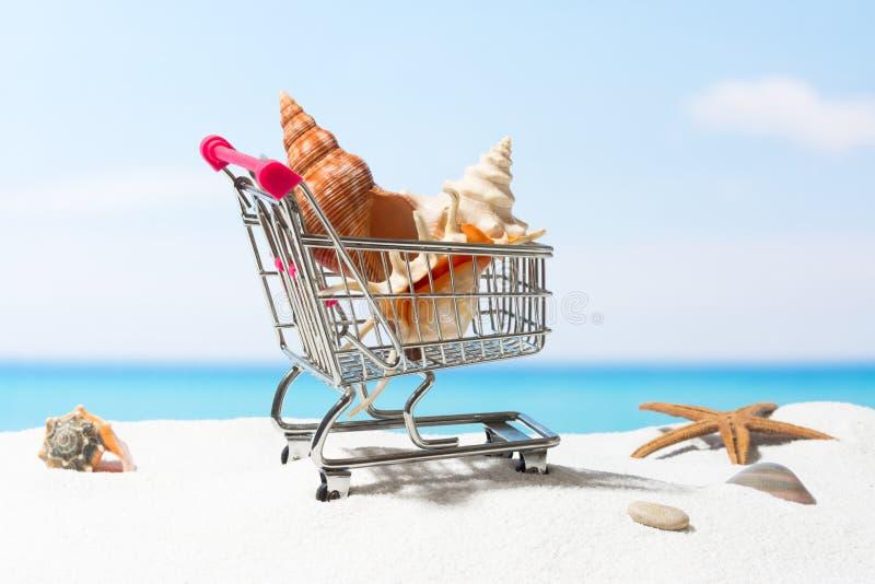 Compras del verano Negocio y venta en la playa Carro en la arena blanca fotos de archivo