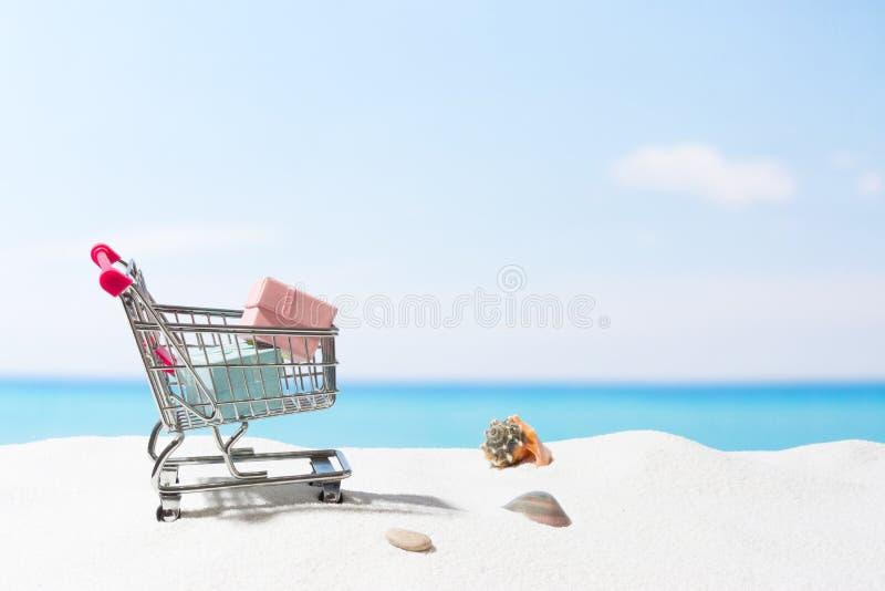 Compras del verano Negocio y venta en la playa Carro en la arena blanca fotografía de archivo
