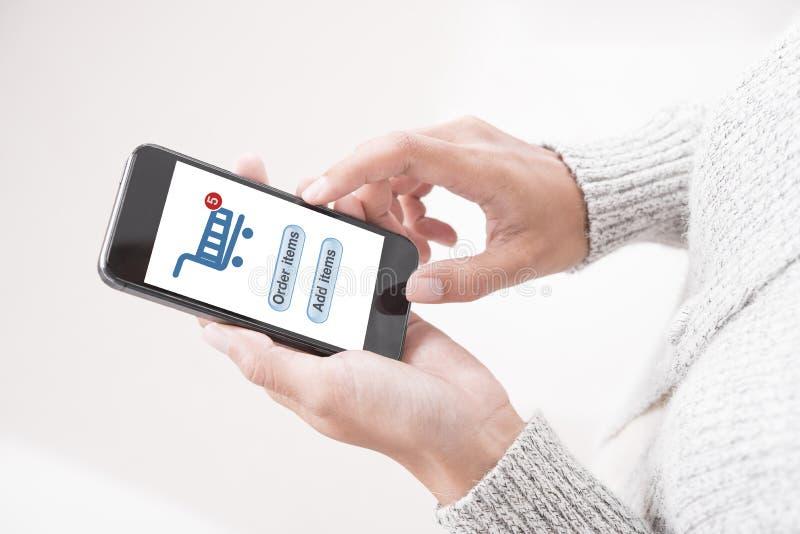 Compras en línea conmovedoras de la mano en comercio electrónico de la aplicación móvil imagen de archivo libre de regalías