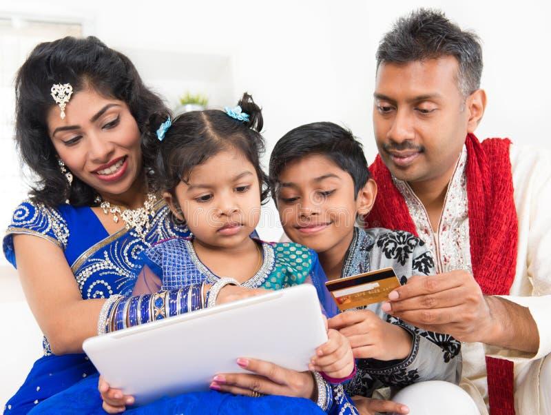 Compras en línea de la familia asiática india con el crédito Ca foto de archivo