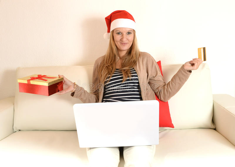 Compras en línea de la Navidad de la mujer con el ordenador y la tarjeta de crédito imagen de archivo libre de regalías