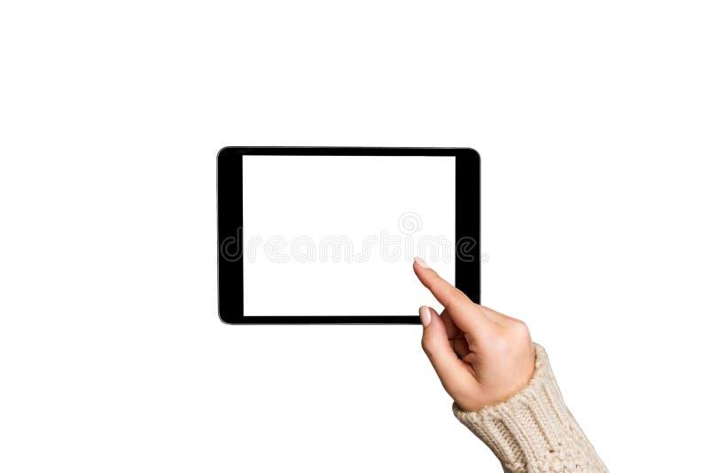 Compras en línea de la Navidad manos femeninas en suéter usando la PC de la tableta con la pantalla blanca, aislada en el fondo b imágenes de archivo libres de regalías