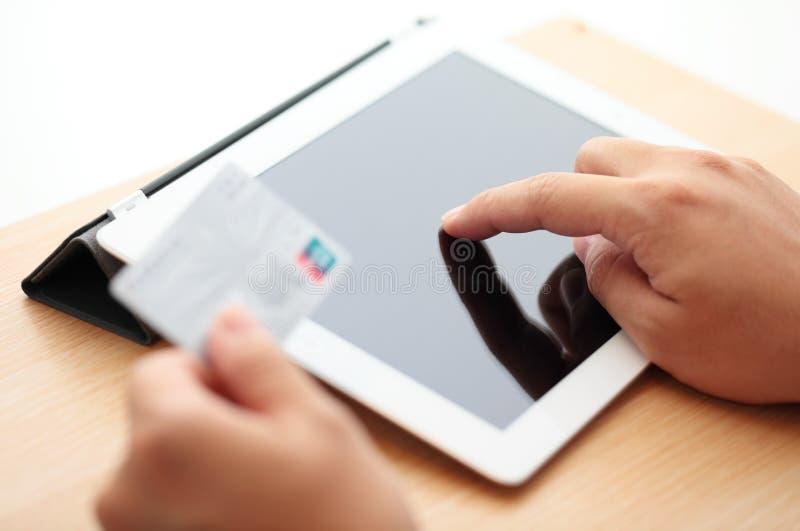 Compras en línea de la tableta con la tarjeta de crédito foto de archivo