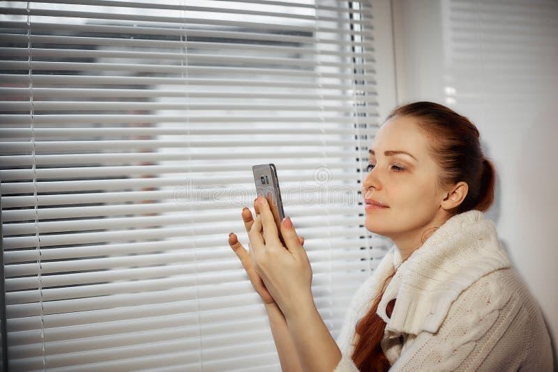 Compras en línea, mujer joven que hojea las mercancías en la tienda en línea en la pantalla del smartphone imágenes de archivo libres de regalías