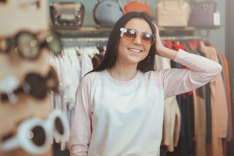 Compras encantadoras de la mujer joven para las gafas fotografía de archivo