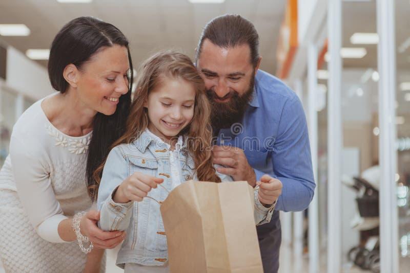 Compras felices de la familia en la alameda junto fotografía de archivo