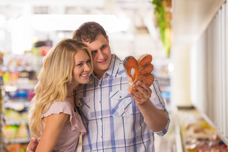 Compras felices de los pares en el supermercado local imagenes de archivo