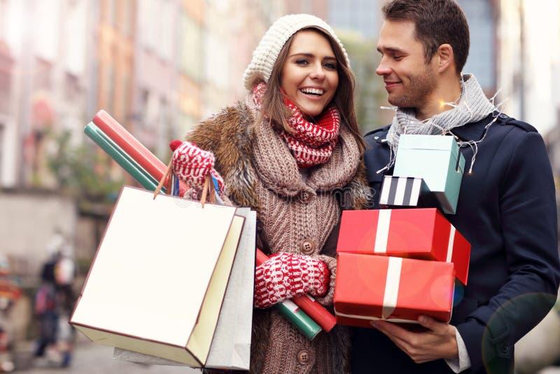 Compras felices de los pares para la Navidad en la ciudad fotografía de archivo