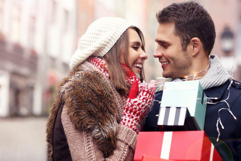 Compras felices de los pares para la Navidad en la ciudad imagen de archivo libre de regalías
