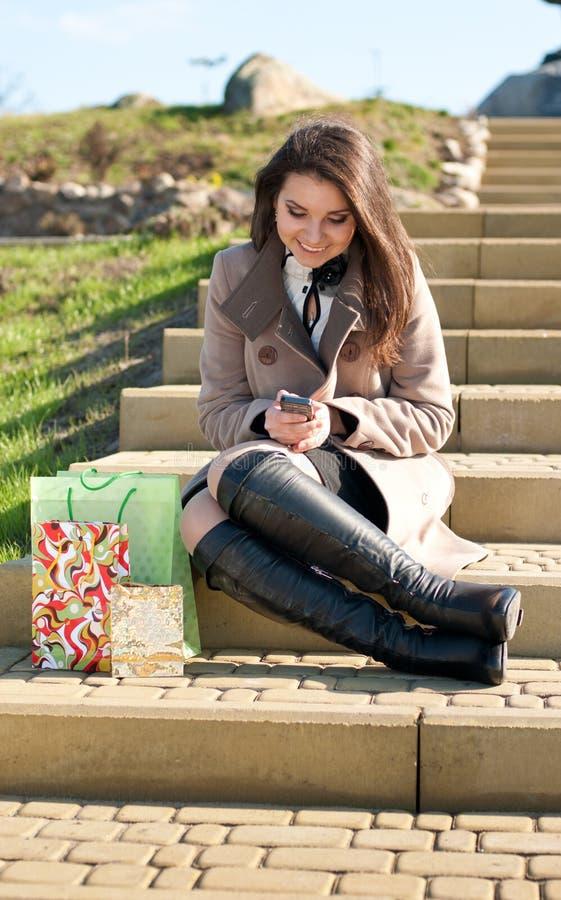 Compras felices: Mujer con su compra y teléfono fotos de archivo