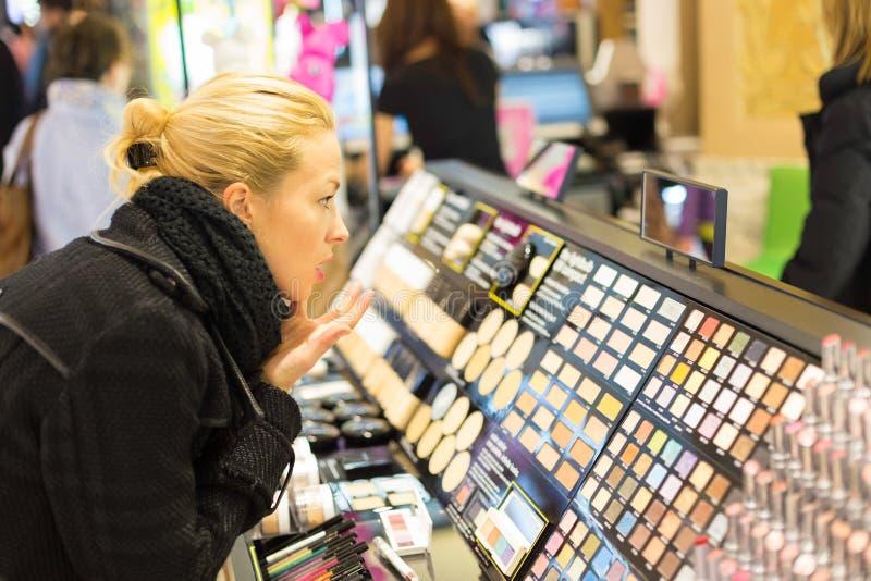 Compras hermosas de la mujer en tienda de la belleza foto de archivo