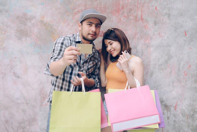 Compras jovenes de los pares con la tarjeta de crédito Mujer asiática feliz y mA fotos de archivo libres de regalías