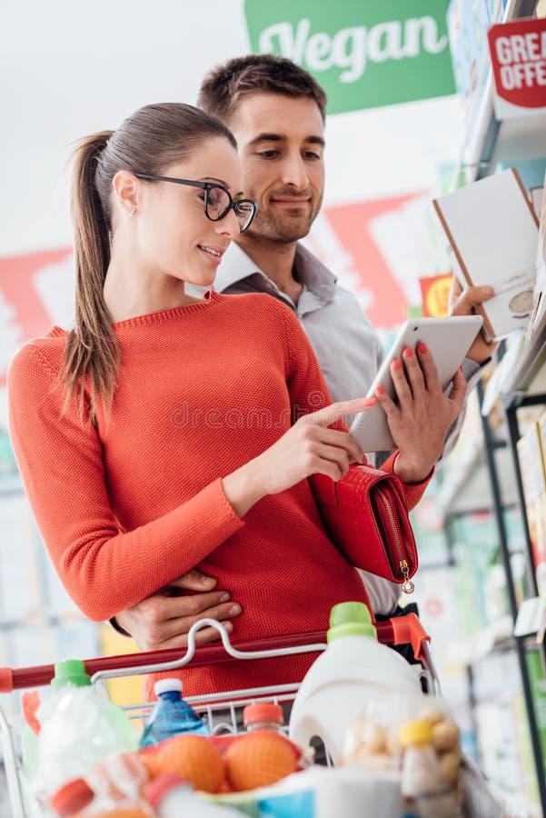 Compras jovenes de los pares con una tableta foto de archivo libre de regalías