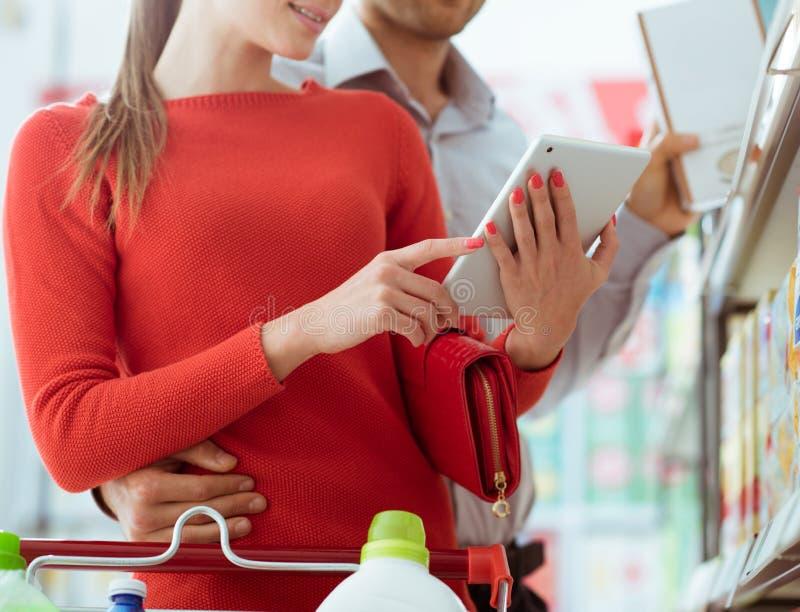 Compras jovenes de los pares con una tableta fotos de archivo libres de regalías