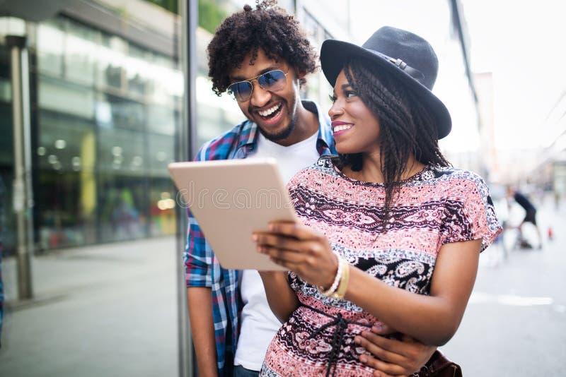 Compras jovenes de los pares en Internet con la tableta fotos de archivo