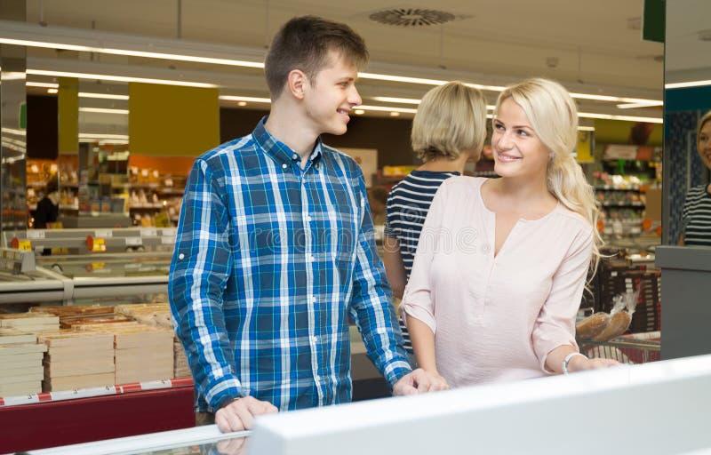 Compras jovenes positivas de los pares en supermercado fotos de archivo