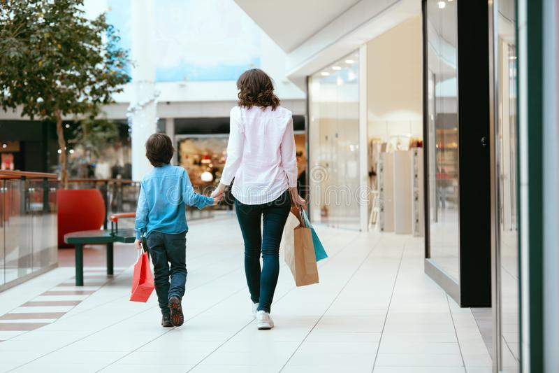 Compras Madre y niño jovenes con los bolsos en alameda foto de archivo