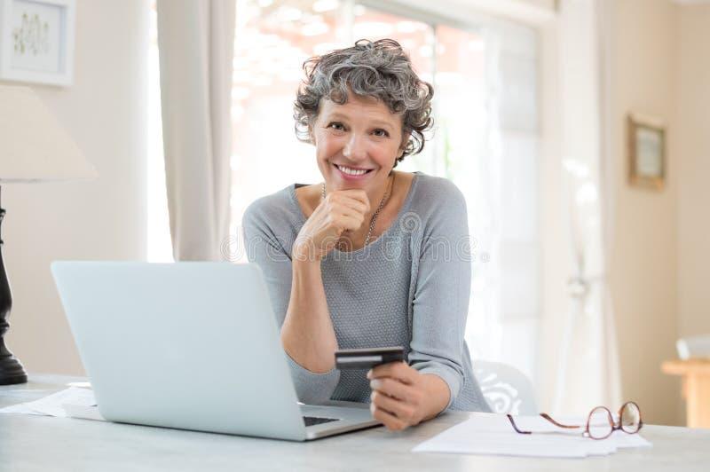 Compras mayores de la mujer en línea fotografía de archivo libre de regalías
