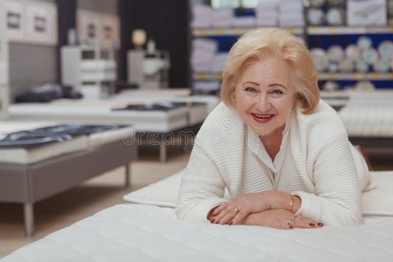 Compras mayores de la mujer en la tienda del mobiliario foto de archivo