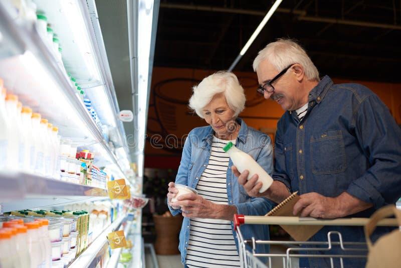 Compras mayores de los pares en supermercado imagenes de archivo