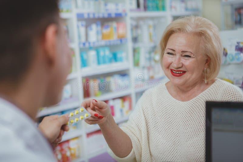 Compras mayores preciosas de la mujer en la droguer?a imagenes de archivo