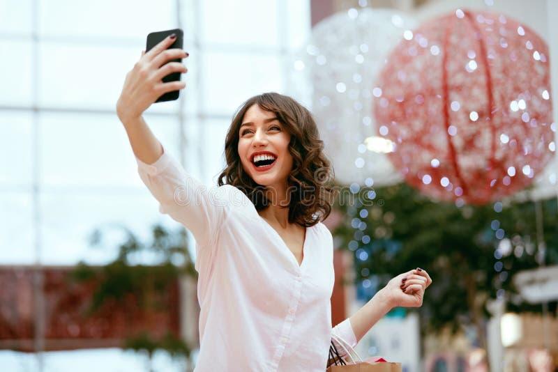 Compras Mujer sonriente que toma las fotos en centro comercial imagen de archivo libre de regalías