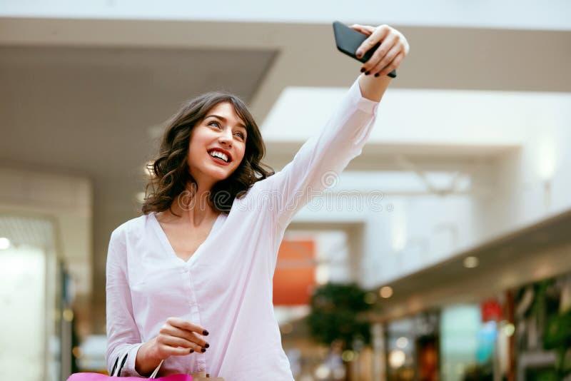 Compras Mujer sonriente que toma las fotos en centro comercial imágenes de archivo libres de regalías