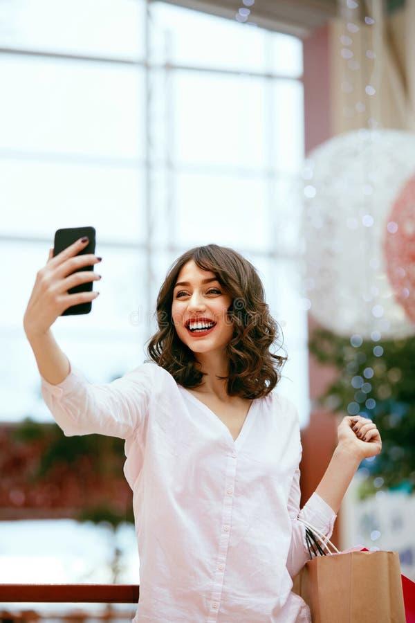 Compras Mujer sonriente que toma las fotos en centro comercial foto de archivo libre de regalías