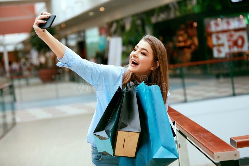 Compras Mujer sonriente que toma las fotos en centro comercial fotos de archivo
