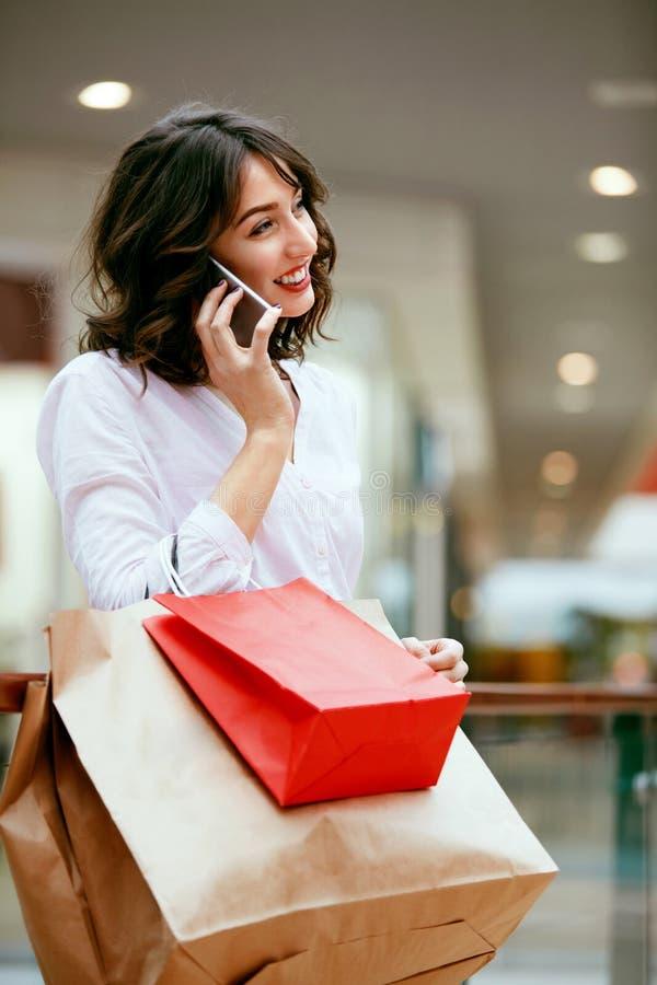 Compras Mujer sonriente que usa el teléfono en centro comercial fotos de archivo