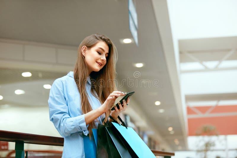Compras Mujer sonriente que usa el teléfono en centro comercial imagen de archivo