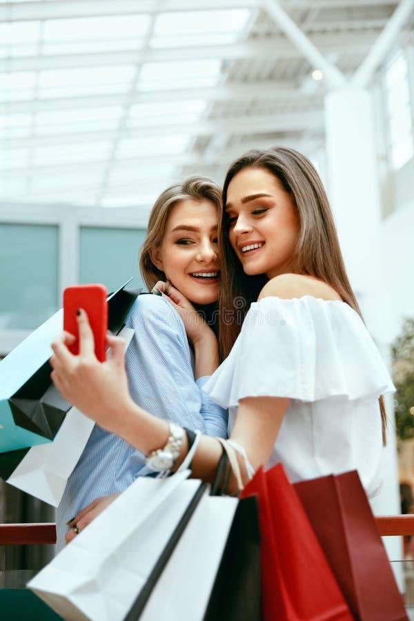 Compras Mujeres sonrientes que toman las fotos en centro comercial foto de archivo
