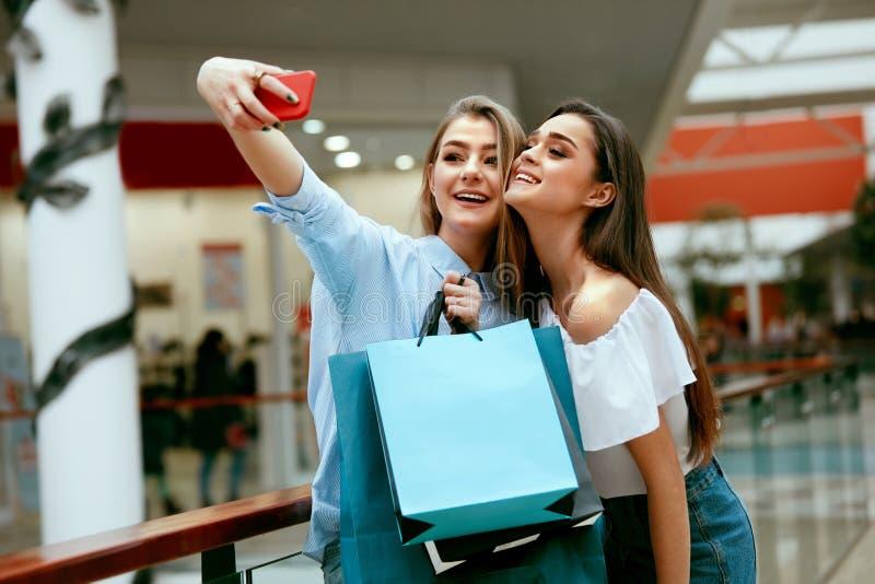 Compras Mujeres sonrientes que toman las fotos en centro comercial fotos de archivo