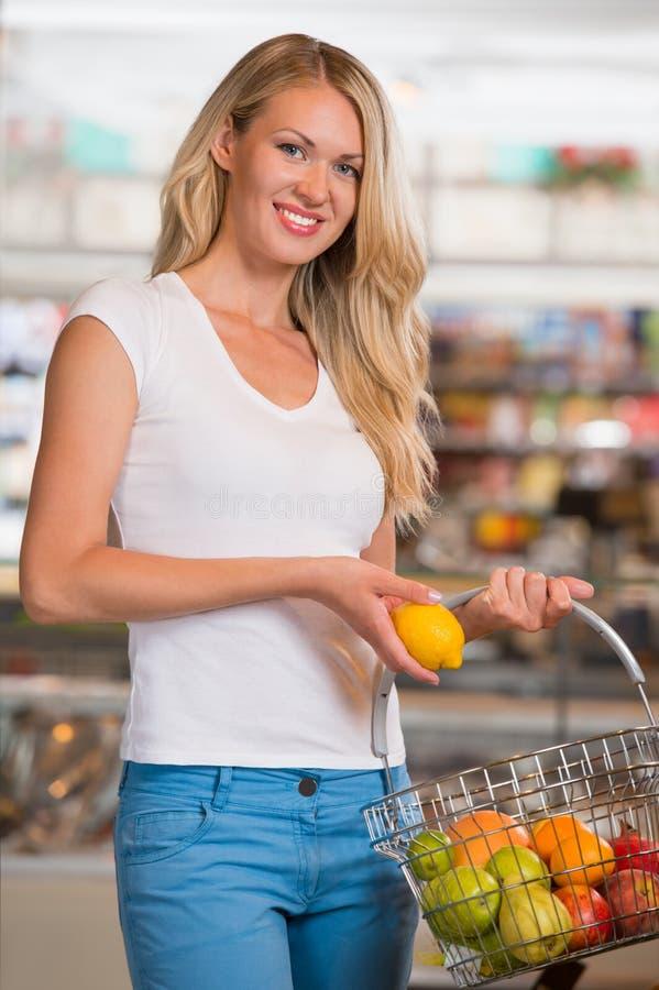 Compras na mercearia ocasionais da mulher na seção do alimento biológico fotos de stock royalty free