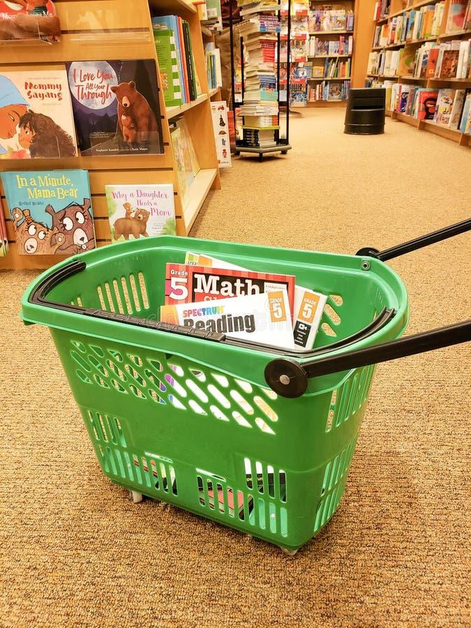Compras para los libros de escuela en una librería para de nuevo a la escuela para un niño o los niños foto de archivo libre de regalías