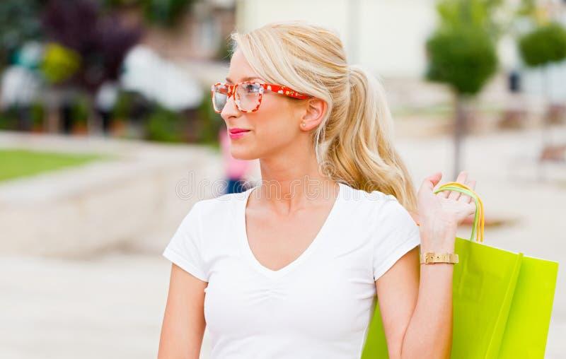 Compras rubias hermosas de la muchacha en ciudad fotos de archivo libres de regalías