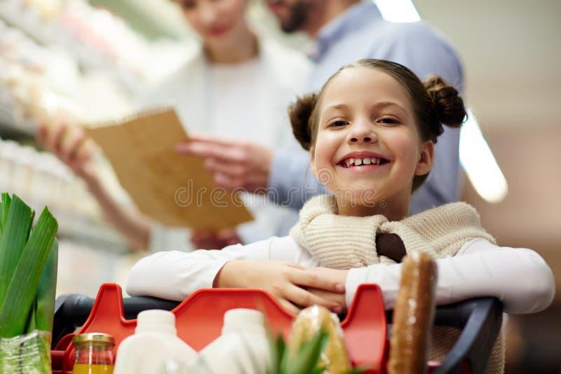 Compras sonrientes de la muchacha con los padres foto de archivo