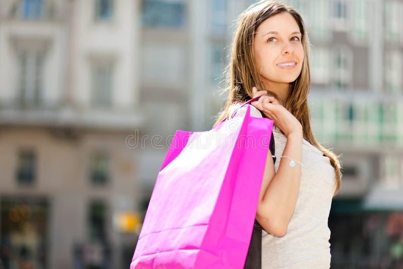 Compras sonrientes de la mujer joven en la ciudad imagen de archivo libre de regalías